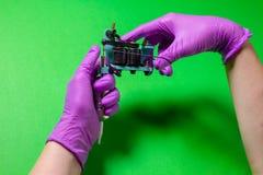 Las manos sostienen una máquina azul del tatuaje Fotos de archivo