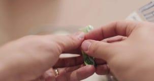 Las manos sostienen una piruleta del caramelo y abren una envoltura de caramelo entonces comen Primera opini?n de la persona almacen de metraje de vídeo