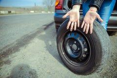 Las manos sucias de la mujer después del ` s del coche ruedan el cambio foto de archivo libre de regalías