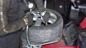 Las manos sucias del trabajador inflan el compresor del ingenio del aire del neumático en la máquina del montaje almacen de metraje de vídeo