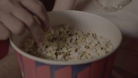 Las manos toman las palomitas de una taza de papel en el cine almacen de metraje de vídeo