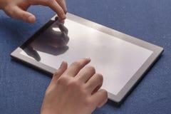 Las manos utilizan la tableta negra en azul fotografía de archivo