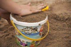 Las manos y el cubo colorido plástico del niño con la arena Foto de archivo libre de regalías