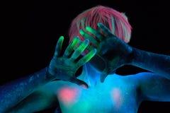 Las manos y el pelo de un modelo de la muchacha pintado con el neón colorearon las pinturas teniendo en cuenta las lámparas ultra Imagenes de archivo