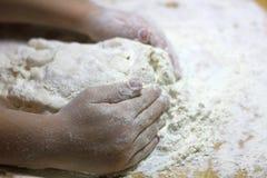 Las manos y la pasta de los ni?os Ni?o peque?o que amasa una pasta Concepto hecho a mano sano de la comida productos de la panade fotografía de archivo libre de regalías