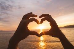 Las manos y los fingeres en corazón forman el sol poniente que enmarca en la salida del sol sobre el océano Imagenes de archivo