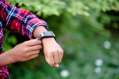 Las manos y los relojes digitales de muchachos miran el tiempo en la muñeca T fotografía de archivo