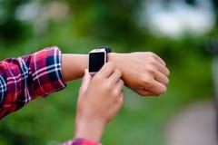 Las manos y los relojes digitales de muchachos miran el tiempo en la muñeca T foto de archivo libre de regalías