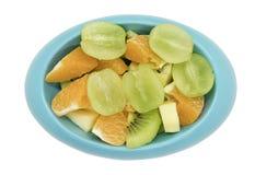 Las manzanas anaranjadas del kiwi de las uvas sin semillas cortaron en pedazos en sh oval azul Foto de archivo libre de regalías