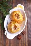 Las manzanas cocieron con la miel y las nueces en una placa blanca Imagen de archivo libre de regalías