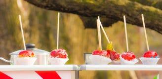 Las manzanas de caramelo rojas coloridas en la comida de la calle atormentan imagen de archivo