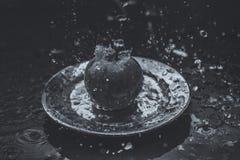 las manzanas en el agua fluyen la situación en la placa al aire libre Foto de archivo