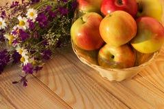 Las manzanas en un florero tejido con el prado florecen en una tabla de madera Foto de archivo