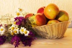 Las manzanas en un florero tejido con el prado florecen en una tabla de madera Fotos de archivo libres de regalías