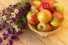 Las manzanas en un florero tejido con el prado florecen en una tabla de madera Imagenes de archivo