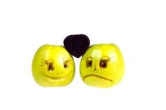 Las manzanas felices y tristes de los emoticons mantienen el caramelo la forma Imagen de archivo