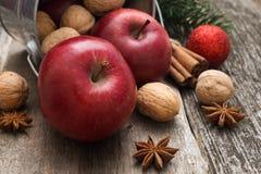 Las manzanas rojas con la Navidad condimentan la decoración encendido woden el fondo Imagenes de archivo