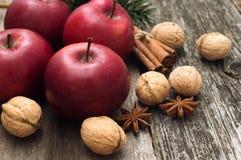 Las manzanas rojas con la Navidad condimentan la decoración encendido woden el fondo Imágenes de archivo libres de regalías