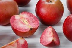 Las manzanas rojas llamadas Redlove están situadas en una superficie de madera fotos de archivo
