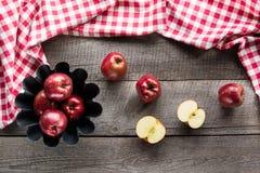 Las manzanas rojas maduras en la hornada forman a bordo con la servilleta a cuadros roja Foto de archivo