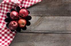 Las manzanas rojas maduras en la hornada forman en el tablero de madera con la servilleta a cuadros roja Foto de archivo