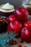 Las manzanas rojas para una Navidad se apelmazan con la harina nuts y los huevos en canela atavían ramas Imagen de archivo libre de regalías