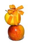Las manzanas rojas y amarillas con un regalo arquean Imagen de archivo libre de regalías