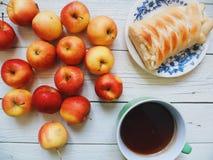 las manzanas rojas y amarillas, una taza de té y la torta hecha en casa con las manzanas mienten sobre la base blanca Imágenes de archivo libres de regalías