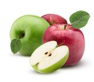 Las manzanas rojas y verdes una cortaron por la mitad con la hoja con descensos del agua Foto de archivo