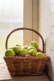 Las manzanas verdes acercan a la ventana Foto de archivo