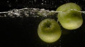 Las manzanas verdes caen en la cámara lenta del primer del agua uno por uno