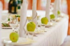 Las manzanas verdes se colocan en las placas vacías en una tabla en restaurante Fotografía de archivo libre de regalías