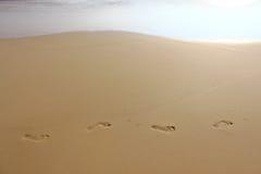 Las marcas de pies en la arena Imagen de archivo libre de regalías