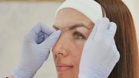 Las marcas del cosmetólogo de la muchacha con la ayuda del tatuaje de la ceja del hilo Maquillaje permanente Tatuaje permanente d almacen de video