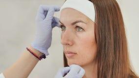 Las marcas del cosmetólogo de la muchacha con la ayuda del tatuaje de la ceja del hilo Maquillaje permanente Tatuaje permanente d almacen de metraje de vídeo
