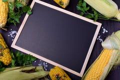 Las mazorcas de maíz crudas y asadas a la parrilla están enmarcando la pizarra fotos de archivo libres de regalías