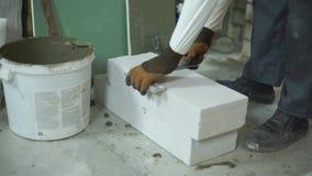 Las medidas del constructor airearon el bloque de cemento con la cinta métrica y el regla de la esquina metrajes