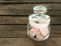Las melcochas rosadas preciosas del corazón en el tarro de cristal Fotos de archivo