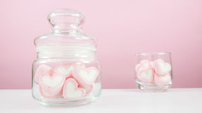 Las melcochas rosadas preciosas del corazón en pequeño tarro de cristal Fotografía de archivo