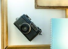Las memorias, diarios, cámaras, enmarcan el cuaderno blanco del fondo Fotos de archivo