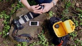 Las mentiras de la cámara y del teléfono en la hierba El fotógrafo recolecta todos en el bolso metrajes