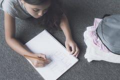 Las mentiras en el piso al lado de su mochila con cosas y dibujan un lápiz en un plan blanco del escape del cuaderno Fotos de archivo