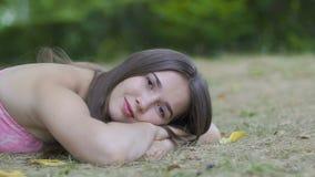 Las mentiras femeninas jovenes en parque miran in camera, soñando a la mujer en hierba comtemplan almacen de video
