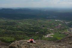 Las mentiras solas de la mujer altas en las montañas disfrutan de la visión foto de archivo