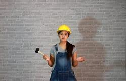 Las mercancías de la mujer del técnico amarillean el casco con la situación gris del vestido del delantal de los vaqueros de la c foto de archivo libre de regalías