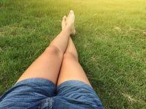 Las mercancías de la mujer ponen en cortocircuito la mezclilla que se sienta en la hierba verde foto de archivo libre de regalías