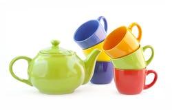 Las mercancías fijaron para el té, café con una tetera verde Imágenes de archivo libres de regalías