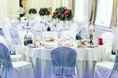 Las mesas redondas sirvieron con cutlary y la comida para una cena festiva Imagen de archivo