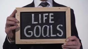 Las metas de la vida escritas en la pizarra en manos del hombre de negocios, éxito inclinan, motivación almacen de video