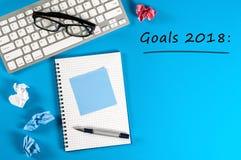 Las metas de la visión superior 2018 enumeran con el teclado, materiales de oficina en el escritorio azul Blancos, meta, sueños y Fotografía de archivo